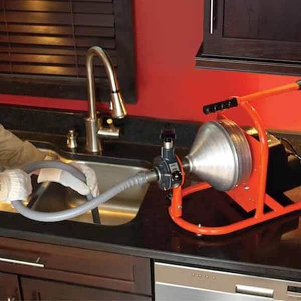 plombier qui débouche un évier avec un furet électrique