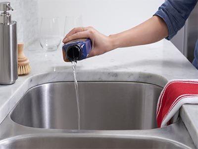 Plombier débouche un évier avec du produit chimique