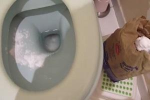 Plombier qui réalise un détartrage wc avec du bicarbonate de soude