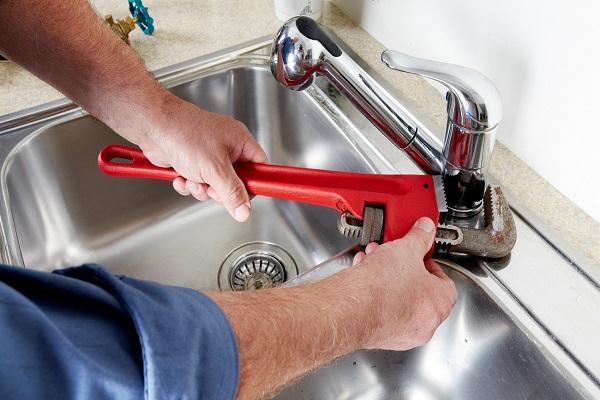 Plombier qui procède à une réparation fuite évier